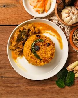 Prato biryani de carneiro indiano servido na mesa de madeira. comida típica da índia, feita com carne de cabra misturada com especiarias e arroz basmati