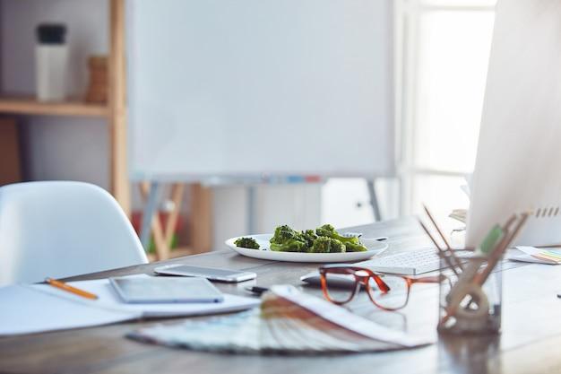 Prato branco com comida saudável na mesa do escritório