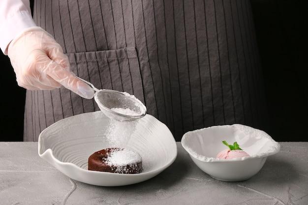 Prato branco com fundente de chocolate close-up. mãos de mulher. o chef faz a sobremesa. receita de bolo de lava