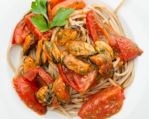 Prato branco com macarrão espaguete, mexilhão e tomate