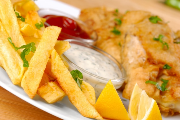 Prato branco com peixe, batatas fritas, maionese, ketchup e limão