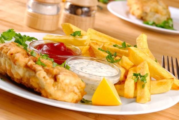 Prato branco com peixe e batatas fritas, maionese e ketchup