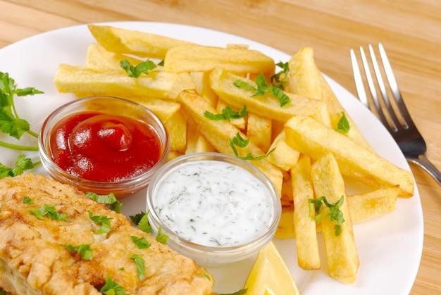 Prato branco com peixe e batatas fritas, maionese, limão e ketchup