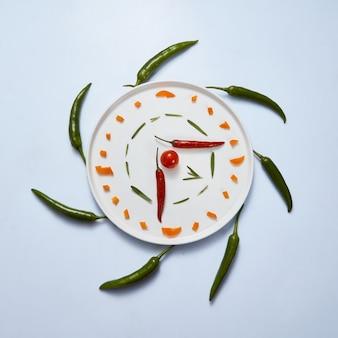 Prato branco com pimentões amarelos e vermelhos fatiados são feitos relógio com tomate e alecrim, ao redor do prato pimentões verdes