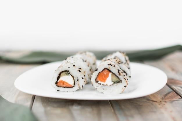 Prato branco com sushi na mesa de madeira