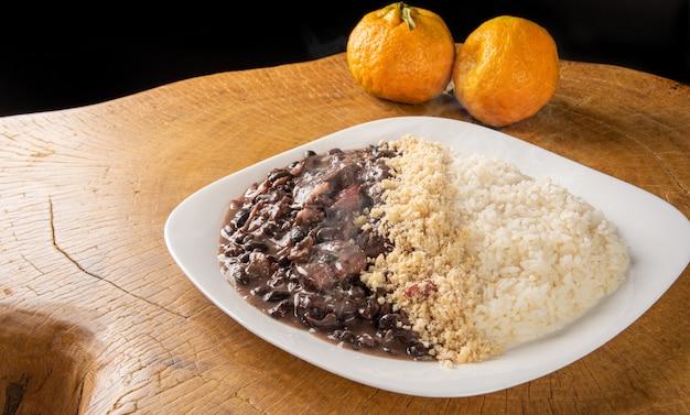 Prato branco com uma deliciosa feijoada brasileira, arroz e farofa, com duas laranjas em madeira rústica