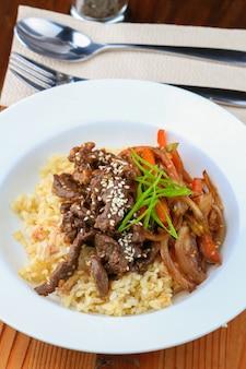 Prato branco de arroz, carne, legumes com temperos e colher e garfo por perto
