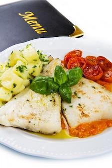 Prato branco de bacalhau preto fresco com molho de batata e tomate