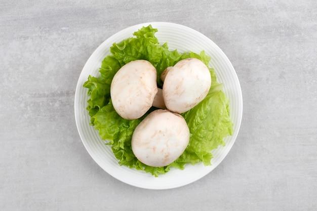 Prato branco de cogumelos brancos frescos e alface na mesa de pedra.