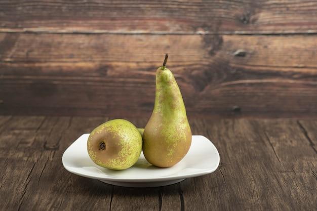 Prato branco de deliciosas peras maduras na superfície de madeira