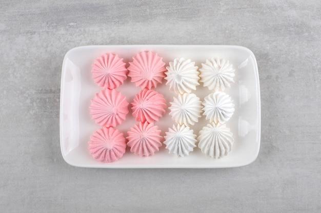 Prato branco de doces de merengue branco e rosa na mesa de pedra.