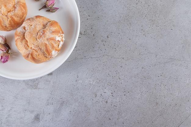 Prato branco de profiteroles doces com rosas na superfície da pedra
