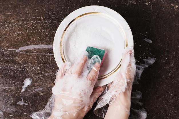 Prato branco, detergente e esponja para pratos em um fundo escuro de mármore. higiene. lave a louça com luvas