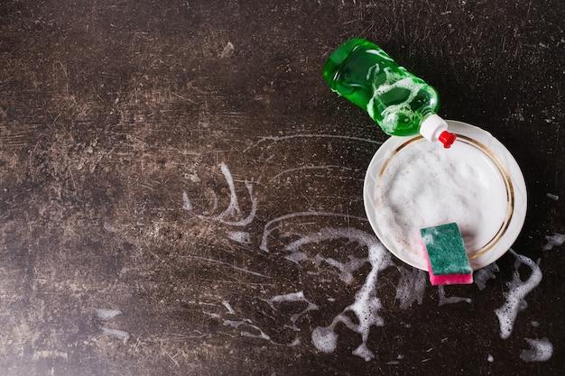 Prato branco, detergente e esponja para pratos em um fundo escuro de mármore. higiene. lave os pratos