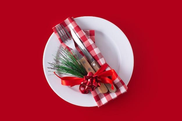 Prato branco, garfo, faca e decoração de natal na superfície vermelha