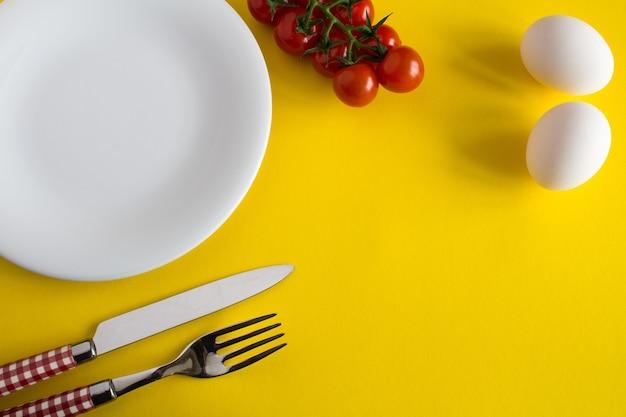 Prato branco, garfo, faca e ingredientes para o café da manhã na superfície amarela. vista superior.