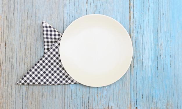 Prato branco na toalha de mesa no fundo da mesa de madeira