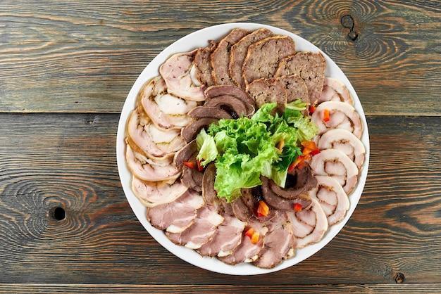 Prato branco sobre uma mesa de madeira cheia de fatias de carne recheada, decorada com folhas de alface frescas e pedaços de páprica.