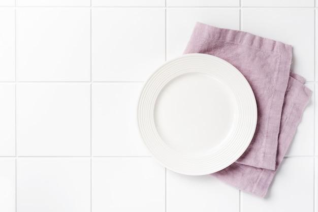 Prato branco, talheres e guardanapo na vista superior da mesa de pedra