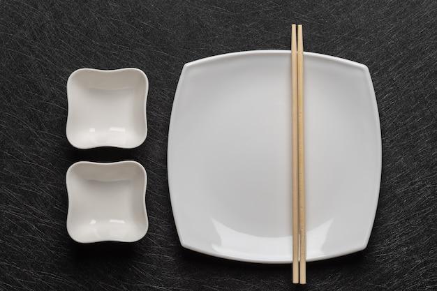 Prato branco vazio com pauzinhos e duas molheiras em um fundo escuro estilo de comida japonesa topo