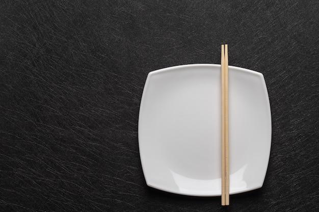 Prato branco vazio com pauzinhos em uma mesa escura. estilo de comida japonesa. vista do topo Foto Premium