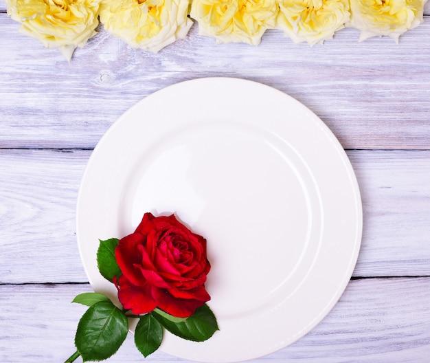 Prato branco vazio com uma rosa vermelha