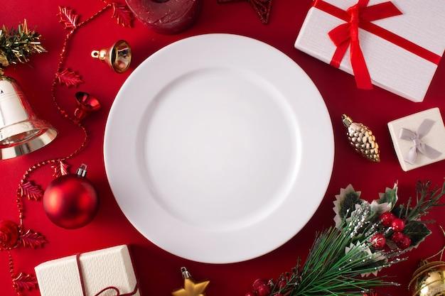 Prato branco vazio e enfeite de natal na superfície vermelha. conceito de jantar de natal.