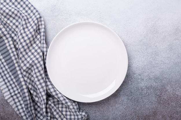 Prato branco vazio e guardanapo de linho em fundo de pedra