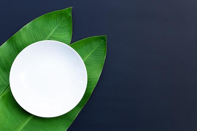 Prato branco vazio em folhas de bananeira tropical