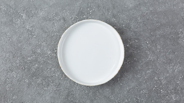Prato branco vazio em um fundo cinza de concreto