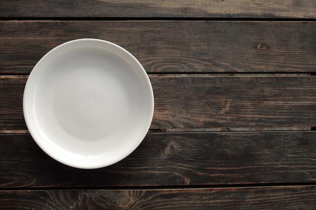 Prato branco vazio em uma mesa de madeira loft. foto de alta qualidade