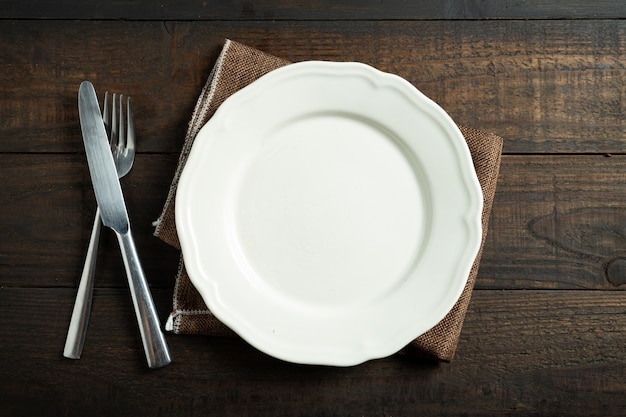 Prato branco vazio na mesa de madeira.