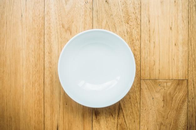 Prato branco vazio no fundo de madeira