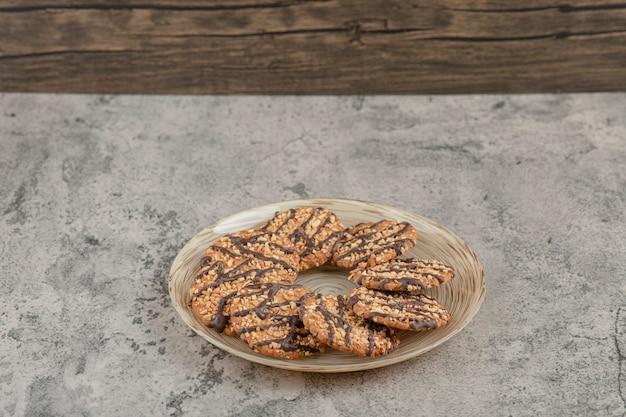Prato cheio de biscoitos doces de aveia com calda de chocolate em um fundo de pedra.