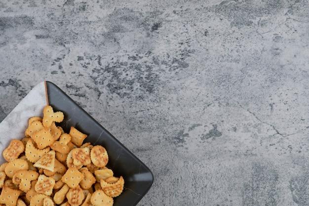 Prato cheio de biscoitos salgados secos no fundo de mármore.