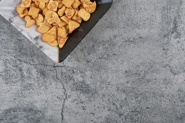 Prato cheio de biscoitos salgados secos sobre mármore.