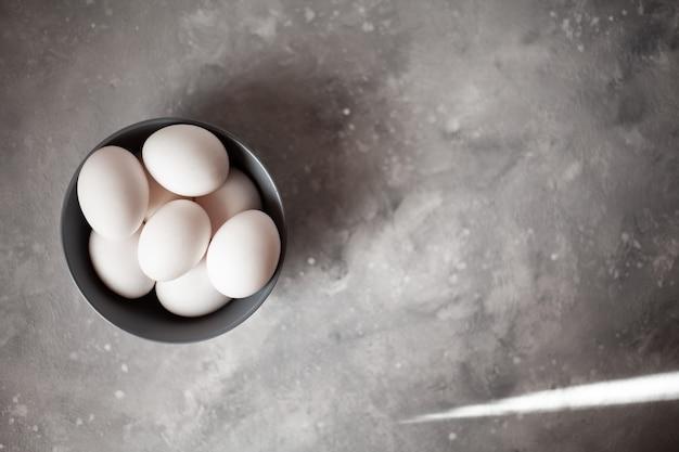 Prato cheio de ovos. mais de quatro ovos. foto tirada sobre fundo de concreto. placa cinza e ovos de galinha. os raios do sol incidem sobre a moldura.