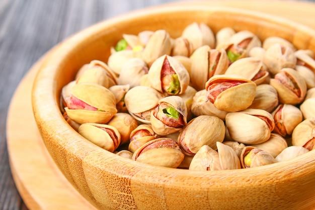 Prato cheio de pistachios com mais pistachios no lado