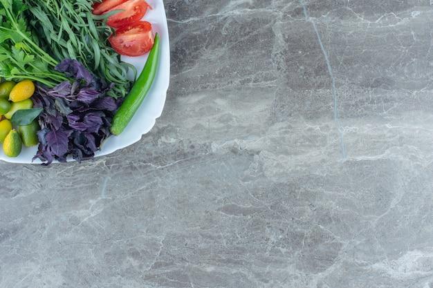 Prato cheio de vegetais misturados, na mesa de mármore.