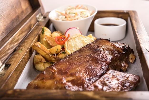 Prato chique com costelas de porco grelhadas, molho de churrasco, batatas fritas, salada de repolho, em uma caixa de madeira