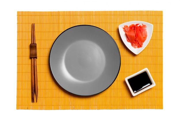 Prato cinza redondo vazio com pauzinhos