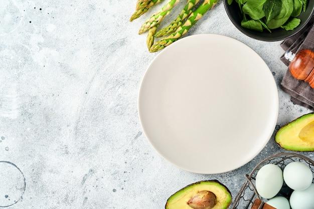 Prato cinza vazio e bando de espinafre de aspargos orgânicos verdes frescos, abacate, ovos de galinha, tempero de pimenta em fundo cinza. configuração da tabela. fundo de cozimento de alimentos com espaço de cópia.