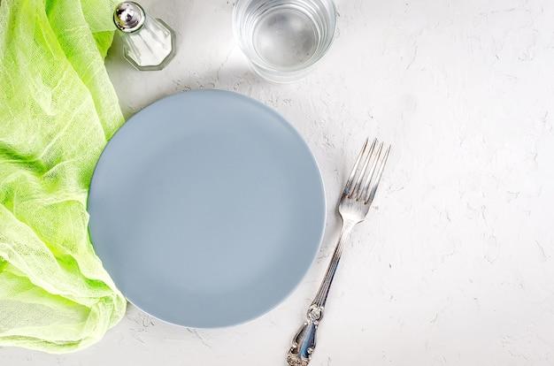 Prato cinza vazio servindo para o jantar e talheres em fundo cinza de concreto.