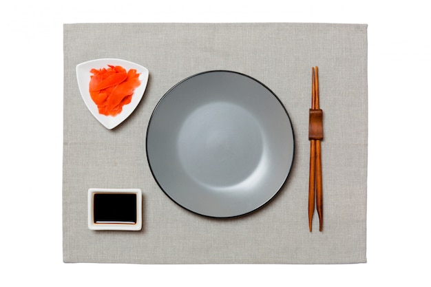 Prato cinzento redondo vazio com pauzinhos para molho de sushi, gengibre e soja no guardanapo cinza. vista superior com copyspace