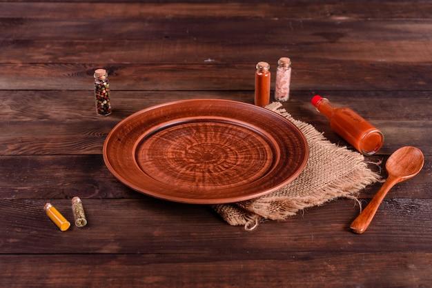 Prato, colher, especiarias e outros acessórios de cozinha em um fundo escuro de madeira