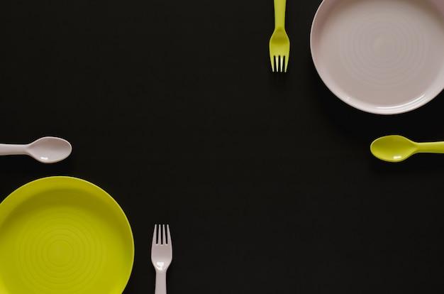Prato colorido com garfo e colher, separados um do outro sobre fundo preto.