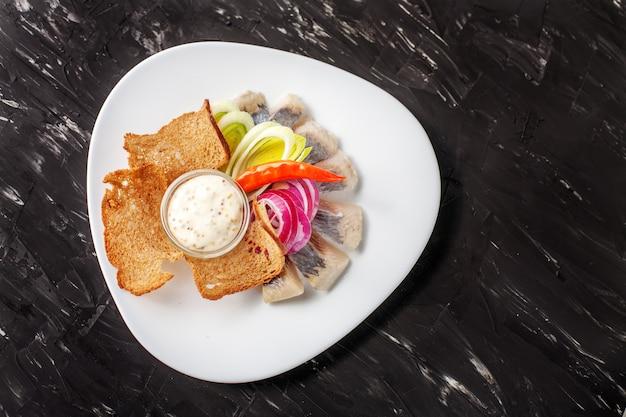 Prato com arenque e pão chips e chili. vista do topo. o conc