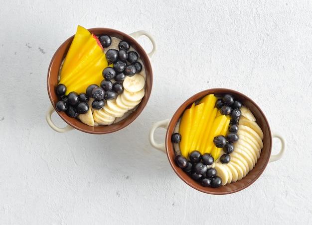 Prato com aveia e manga, mirtilo, banana em uma vista superior branca. mesa de café da manhã saborosa e saudável