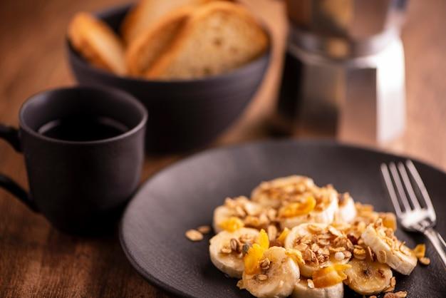 Prato com banana fatiada com granola, frutas cristalizadas e mel, torradas e uma xícara de café