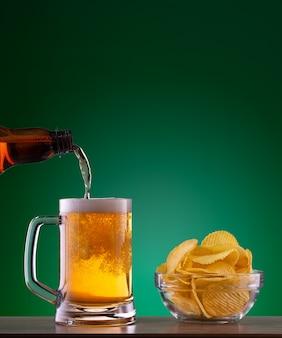 Prato com batatas fritas e cerveja light despejando caneca sobre fundo verde